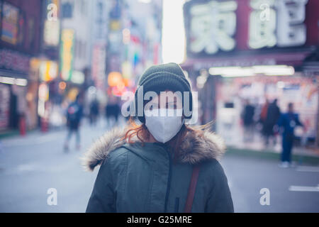 A young caucasian woman is wearing a face mask in Japan - Stock Photo