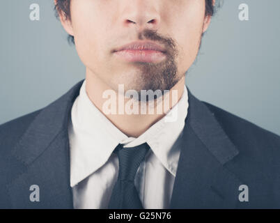 A young businessman with a half shaved beard - Stock Photo