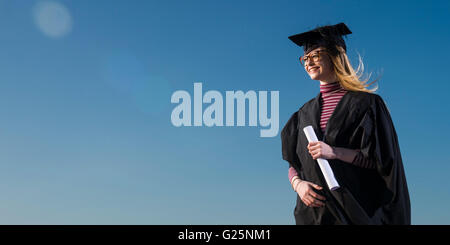 Blue sky thinking: A happy young woman student wearing a university cap mortar board and gown on her graduation - Stock Photo