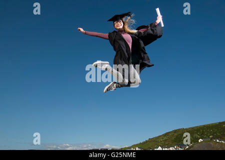 Jumping for joy: A happy young woman girl student wearing a university cap mortar board and gown on her graduation commencement day holding her degree certificate jumping for joy in the air  celebrating her success, UK