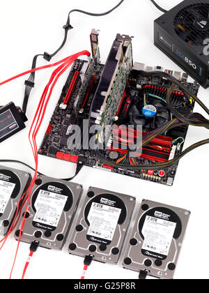 Computer motherboard with four hard drives connected to a RAID controller - Stock Photo