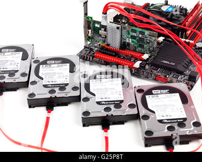Four hard drives connected to computer motherboard with a RAID controller - Stock Photo