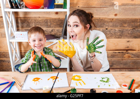 Smiling little boy and his mother having fun and showing hands painted in colorful paints - Stock Photo