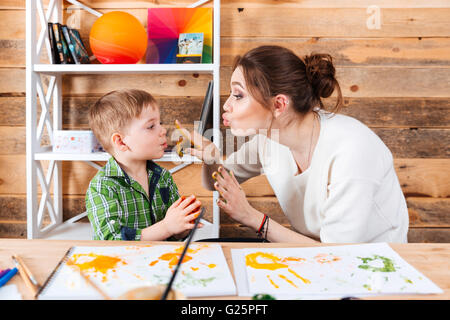 Happy mother touching face of her little son with hands painted in colorful paints and having fun together - Stock Photo