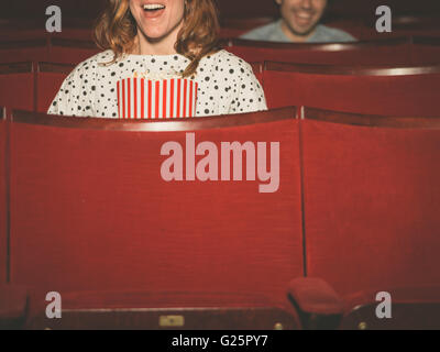 A couple of people are watching a film in a movie theater - Stock Photo