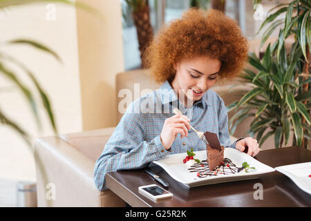 Cute curly young woman with red hair eating dessert in cafe - Stock Photo