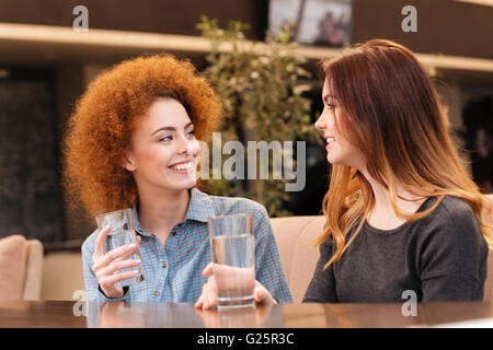 Two happy attractive young women smiling and drinking water in cafe - Stock Photo