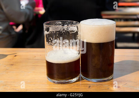 Detail of glasses of german alt beer, typical from dusseldorf, one full glass showing the foam and other almost - Stock Photo