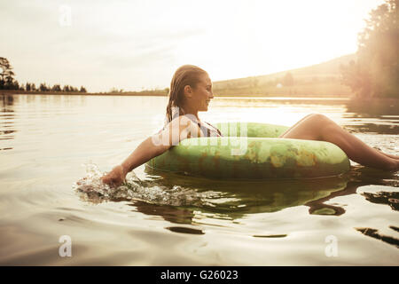 Side portrait of happy young woman in lake on inflatable ring. Young girl relaxing in water on a summer day. - Stock Photo