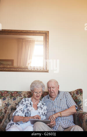Vertical indoor shot of retired couple at home using digital tablet. Senior caucasian man and woman sitting together - Stock Photo