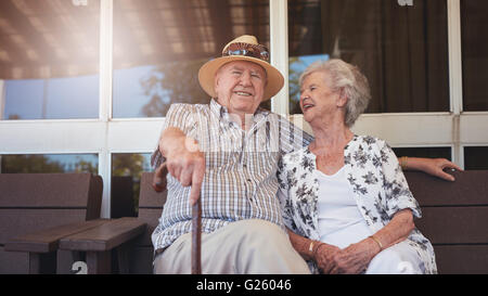 Portrait of handsome senior man sitting with his wife on a bench outside their house. Retired couple taking a break - Stock Photo