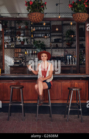 Full length indoor shot of beautiful young woman sitting at a cafe with a drink. Caucasian female relaxing at a - Stock Photo