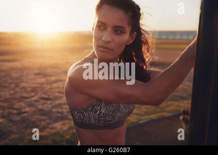 Close up shot of fit young woman in sports bra looking away. Pensive fitness female standing outdoors on a sunny - Stock Photo