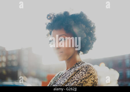 Young woman with afro smiling in urban setting - Stock Photo