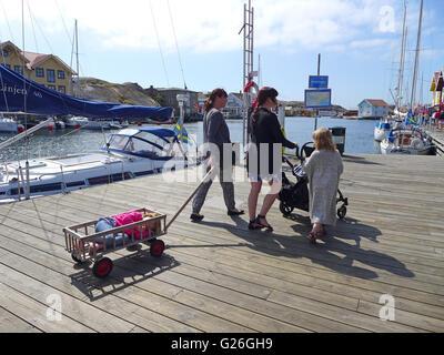 Sweden, Smögens Hafvsbad, family pulling girl in cart - Stock Photo