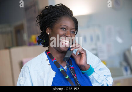 Hospital nurse smiling and speaking on the telephone in her ward - Stock Photo