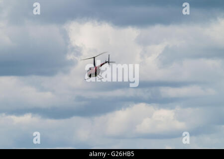 A Robinson R44 helicopter takes off into stormy, cloudy skies at Elstree Airfield in Hertfordshire, UK. - Stock Photo