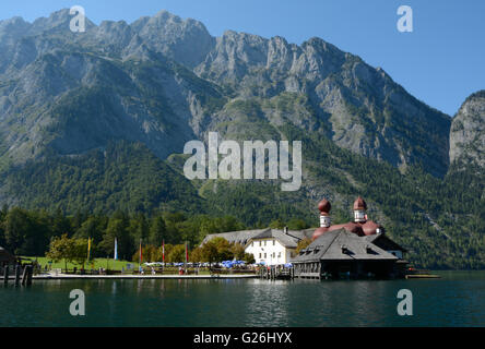 Schonau am Konigssee, Germany - August 30, 2015: Mountains, St. Bartholoma church and other buildings at Koenigssee lake nearby