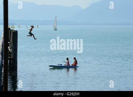 Seebruck, Germany - September 1, 2015: Two unidentified kids on kayak and girl jumping from high pier to water in - Stock Photo