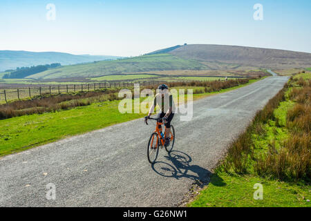Cyclist on the lonely road over Cold Fell in the western fringes of the Lake District - Stock Photo