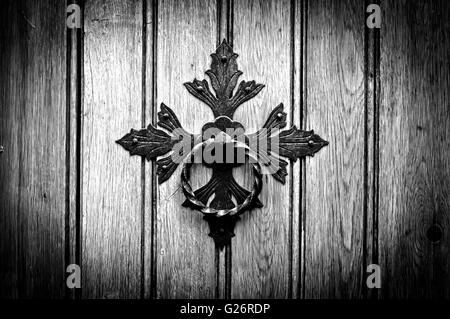 Antique door knocker on old door. Black and white photo - Stock Photo