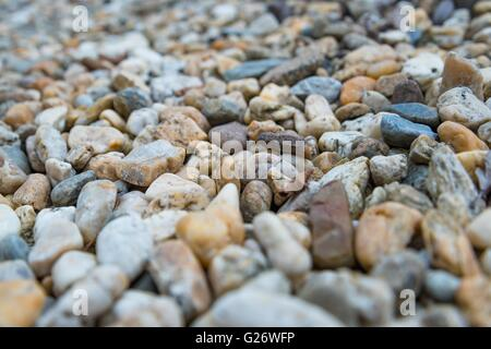 Background of colorful beach pebbles of different shape and size. Shallow DOF. Selective focus. - Stock Photo