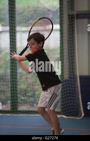 Young boy playing tennis about to hit his forehand - Stock Photo