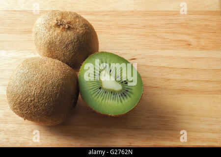 Fresh Kiwi Fruits on a Wooden Board - Stock Photo