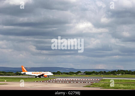 Easyjet Airbus A320-214 taxis out to runway under cloudy sky at Manchester International Airport - Stock Photo