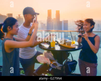 Young people relaxing in the Marina Bay Sands skypark - Stock Photo