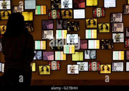 Woman looking at a collage of digital images on LCD screens, Mashup: Roots of Modern Culture exhibit, Vancouver - Stock Photo