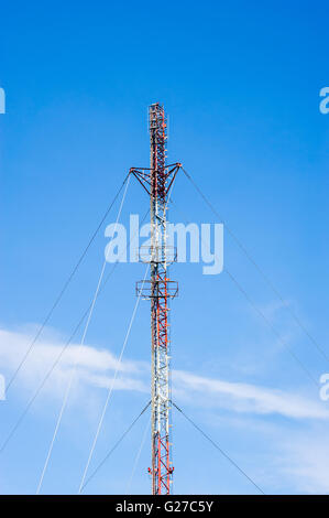 Tall red and white metal communications antenna tower with several supporting cables, against blue sky. - Stock Photo