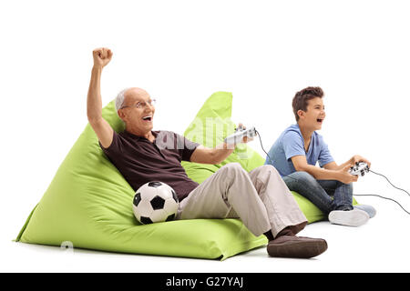 Studio shot of a senior man playing video games with his grandson isolated on white background - Stock Photo