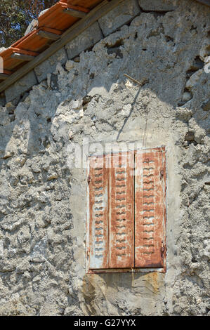 old rusty metal shutters with cut out flying bird shape vents closed on a rough cement concrete render wall with - Stock Photo