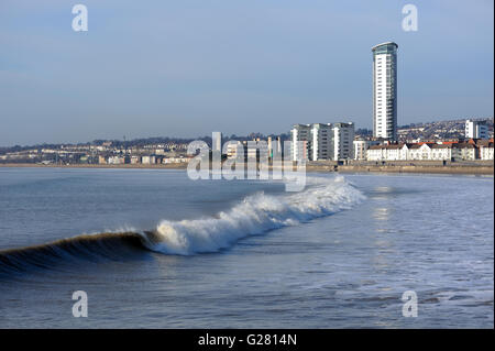 Wave breaking onto the beach at Swansea Seafront close to the site of  proposed Tidal lagoon. Swansea tower stand - Stock Photo