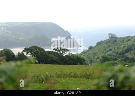Hazy blue skies separate the distinctive Three Cliffs Bay on Gower from the surrounding green fields and trees. - Stock Photo
