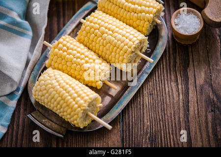 high angle shot of sweetcorn cob ready for bbq, on wooden table - Stock Photo