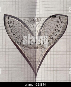 Love Maths! A protractor in sunlight on folded graph paper, the shadow depicting a heart. - Stock Photo