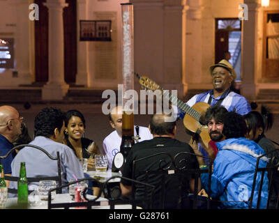 A traditional Cuban musician guitarist entertains people drinking at an outside bar on Plaza Vieja, Havana, Cuba. - Stock Photo