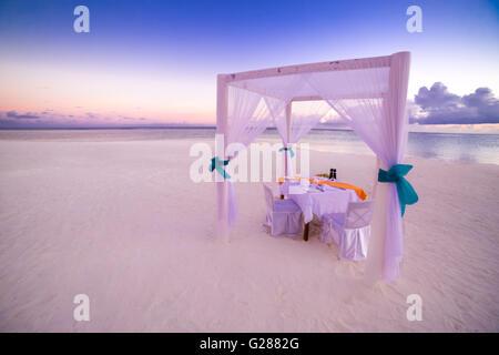 Romantic dinner setting on the beach at sunset, honeymoon background - Stock Photo