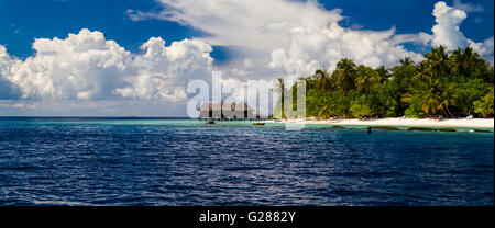 Over water bungalows on a tropical island with palm trees and amazing vibrant beach. Tropical panorama background - Stock Photo
