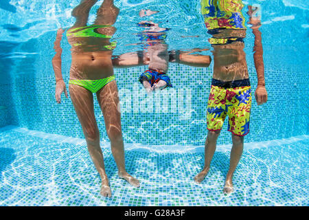 Happy swimming family - father and mother with baby swim and dive underwater with fun in pool. Healthy lifestyle, - Stock Photo