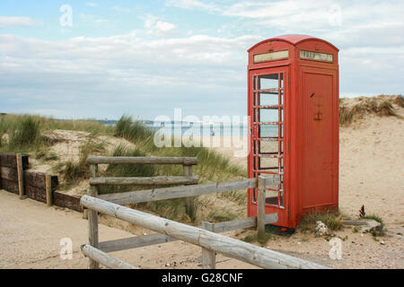An old red telephone box stands among dunes on the edge of a sandy beach with a lone walker under a cloudy sky, - Stock Photo