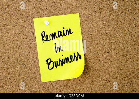 Remain In Business written on yellow paper note pinned on cork board with white thumbtack, copy space available - Stock Photo