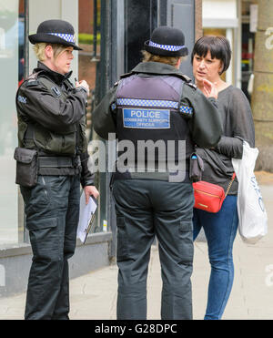 Police community support officers speaking to a pedestrian in a town in the UK.
