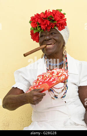 A common sight in the old city of Havana in Cuba - normally an elderly lady will dress in traditional clothes 'smoking' - Stock Photo