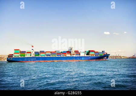 Ship loaded with colorful containers in blue sea - Stock Photo