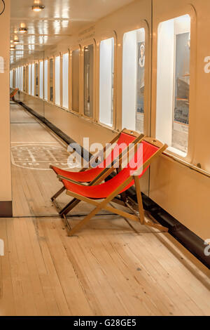 Red deckchairs, part of an exhibition called ''Travelling for pleasure- tourism between the wars'', at the Cobh - Stock Photo