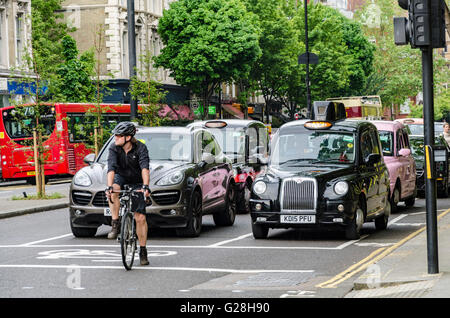 A cyclist waits at the head of a queue at a red traffic light in London ahead of cars and taxis. - Stock Photo