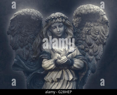 female angel with roses tiara and large feathered wings holding a dove in her hands - Stock Photo